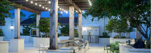 Evening view of AMLI Dadeland Rooftop gazebo with barbeque grilling area and patio furniture bordered by lush landscape