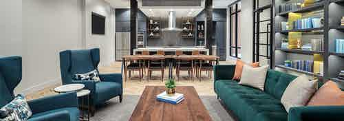 Tap room at AMLI Addison with a teal couch in front of a wall shelf with two chairs across and a wooden coffee table