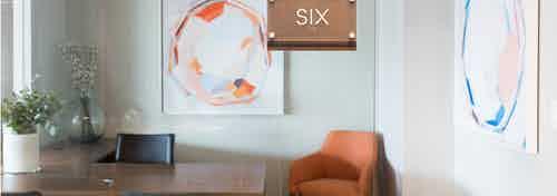 AMLI 3464 private office with a wood desk and an orange office chair in the corner matching a large hanging wall art piece
