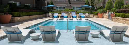 Daytime view of AMLI River Oaks pool with white lounge chairs in the pool with blue pillows attached and surrounding greenery