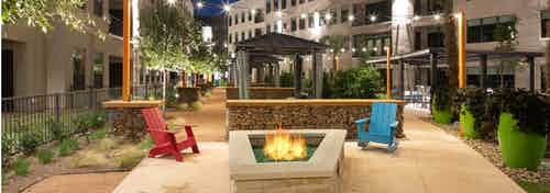 Fire pit on pavement at AMLI on Aldrich with one blue and one red chair surrounded by potted plants and greenery at night