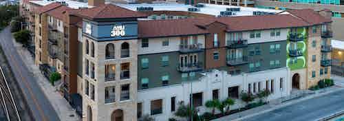 Exterior view of AMLI 300's white, tan, and green exterior building facade