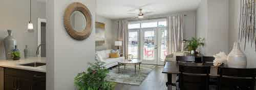 AMLI South Shore living room with dark hardwood and elegant decor with balcony doors revealing bright daytime view