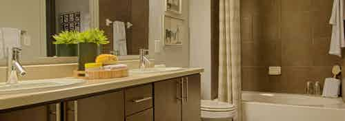 AMLI Uptown apartment bathroom with double vanity, large mirror, dark wood cabinets and garden tub with tile surround