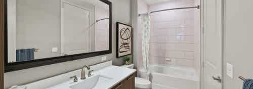 Interior view of AMLI 8800 apartment bathroom with large single vanity, sink with faucet, mirror, toilet and soaking tub
