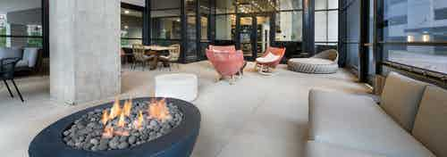 Interior view of AMLI Lenox screened in common space with fire pit and multiple seating areas with brightly colored chairs