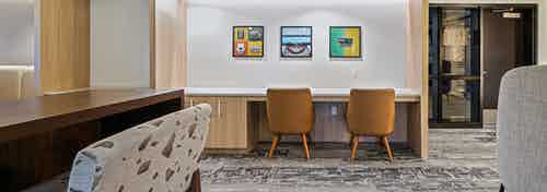 Interior view of AMLI Bellevue Park business center with gray carpet and 2 brown chairs at desk and wood slat ceiling