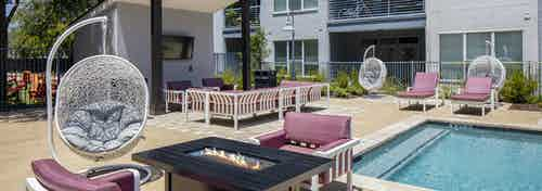 AMLI South Shore poolside outdoor living room with couch seating and TV and a firepit with 3 hanging basket swing chairs