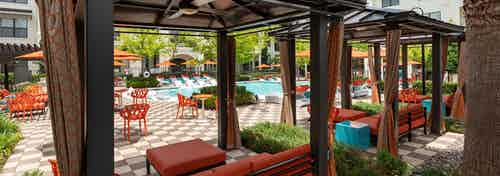 Cabanas at the AMLI on Riverside pool with covered orange couches with foot rests and a daytime view of the swimming pool
