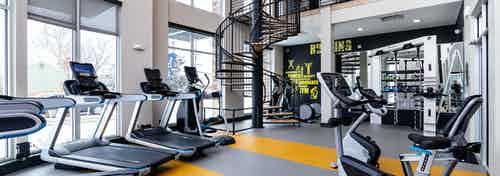 Fitness center at AMLI Littleton Village apartments with cardio machines, motion cage and spiral staircase to upper gym level