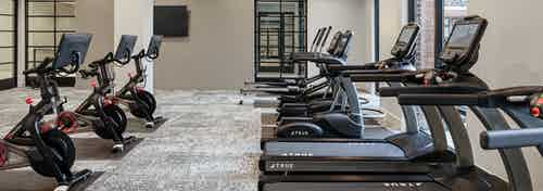 Interior of fitness center at AMLI Addison with treadmills facing large windows and exercise bikes in the row behind