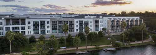 An aerial view at sunset of AMLI South Shore exterior façade with people kayaking in the lake and enjoying the walking trail