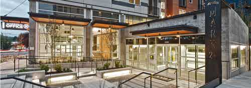 Exterior of AMLI Mark24 apartment community entrance at dusk with view of lobby and leasing office and sidewalk and street