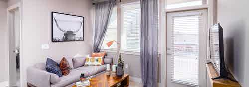 Interior daytime view of AMLI Littleton Village apartment living room with gray cozy couch, coffee table and big screen TV