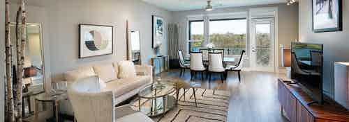 AMLI South Shore living room with light walls and floor to ceiling windows and a door leading to balcony with scenic view