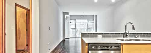 Interior view of an updated AMLI 535 apartment upgraded kitchen and living space with large window and laminate floors