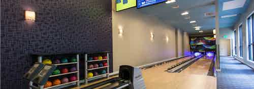 Interior of the two lane bowling alley at AMLI Dadeland apartment's equipped with colorful bowling balls and tv screen