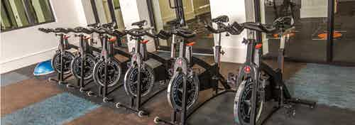 Interior of spinning room at AMLI Joya with multiple spin bikes and full mirrored wall