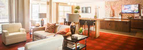 A clubhouse at AMLI Interlocken apartments with several plush couches and chairs with a red carpet and a television