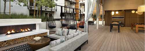 Exterior daytime view of lanai at AMLI Marina Del Rey apartments with fireplace, comfy sectional and teardrop hanging chairs
