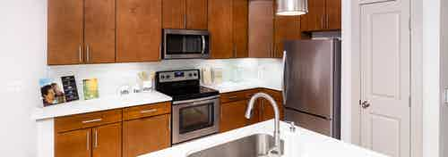 Interior view of a renovated kitchen island at AMLI Park Avenue apartments with white counter tops and many kitchen cabinets