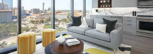 AMLI Fountain Place living room with gray couch and coffee table next to large wall of windows and light gray kitchen behind
