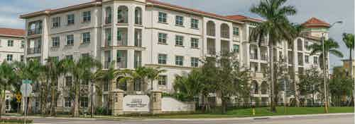 Exterior of AMLI Sawgrass Village apartment community with balconies and palm trees around the building on a green lawn