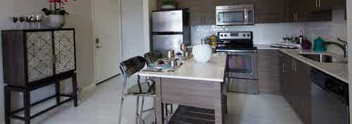 Interior view of AMLI Dadeland apartment island kitchen with stainless steel appliances and dark wood cabinetry
