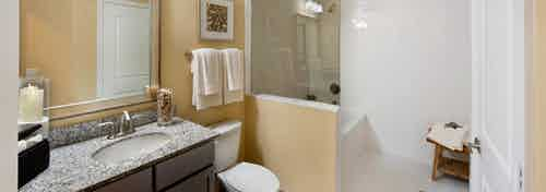 Interior view of AMLI Doral apartment bathroom with single vanity, mirror, towel rack above toilet and soaking tub