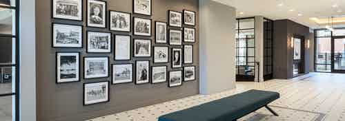 Close up of gallery at AMLI Addison with black and white photo frames of varying sizes hung on a dark wall with a long bench