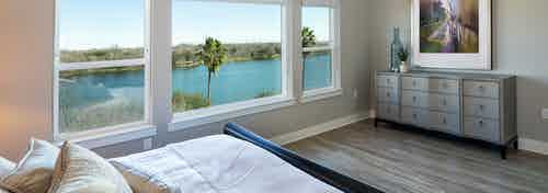 AMLI South Shore bedroom with long windows overlooking Lady Bird Lake and light hardwood with neutral walls and decor