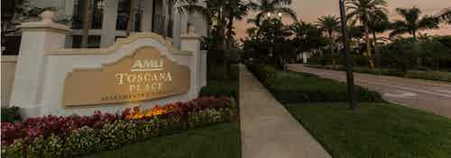 Exterior of AMLI Toscana Place apartment community at dusk with lush landscape, palm tree walkway and back lit monument sign