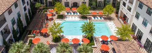 Sunny daytime aerial view of the pool at AMLI on Riverside with vibrant trees and orange umbrellas lining the poolside