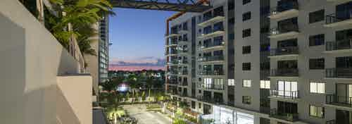 Dusk exterior view of AMLI Midtown Miami apartment buildings with balconies and connecting bridge and lush landscaping below