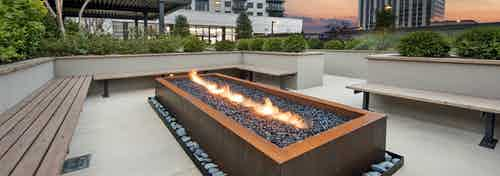 Evening view of outside seating area at AMLI Lenox with lit rectangular fireplace surrounded by brown benches for seating