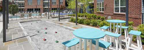 Daytime view of AMLI Decatur with bocce ball court next to high top teal tables and stools overlooking pool and building