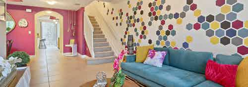 AMLI Toscana Place townhome apartment living room with colorful wall mural and vibrant decor, sofa and peek up the staircase
