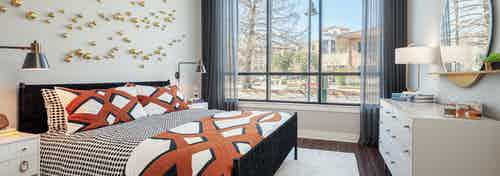 AMLI Addison bedroom with large windows and sheer black curtains with dark hardwood and patterned orange and white bedding