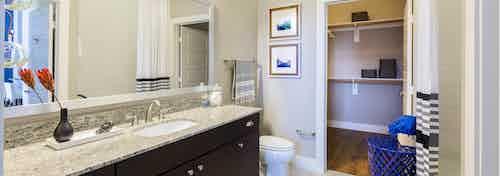 AMLI on Riverside bathroom with dark wood vanity sink with a granite countertop and toilet with peek into walk in closet