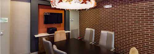 Interior close up view of AMLI RidgeGate conference room with large wood table and chairs equipped with big screen TV and printer