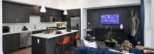 Interior of AMLI Marina Del Rey kitchen island with fully set quartz countertop, dark cabinets and blue sofa in living room