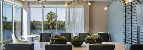 AMLI South Shore resident dining room with wood table and 8 chairs and floor to ceiling windows showcasing Lady Bird Lake