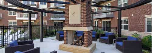 Exterior view of courtyard fireplace with several blue cushioned sitting areas at AMLI Deerfield apartment community