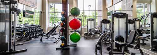 Interior of the fitness center at AMLI Riverfront Park apartments with medicine balls and a variety of workout equipment