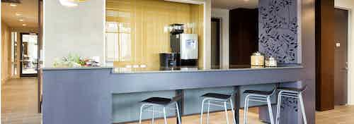Close up of AMLI West Plano java cafe with a blue grey counter and black barstools with coffee machine and ample counterspace