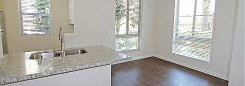 Interior daytime view of AMLI Warner Center apartment kitchen and breakfast nook with hardwood floors and large windows