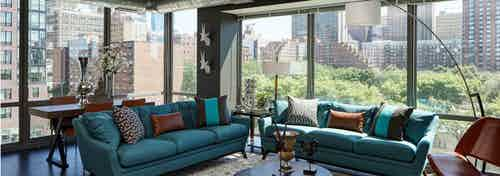 A luxurious AMLI 900 living room which features large glass windows overlooking surrounding city buildings and bright foliage