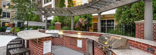 Outdoor kitchen area at AMLI North Point with red brick under white wrap around countertops with a grill and barstools
