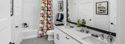 AMLI Decatur apartment bathroom with a white double vanity with a framed mirror and soaking tub with patterned curtain
