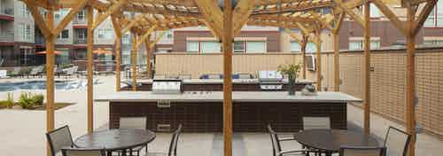 Exterior view of a grilling area at AMLI Littleton Village pool with 2 grills and 2 tables with chairs and a large wood canopy